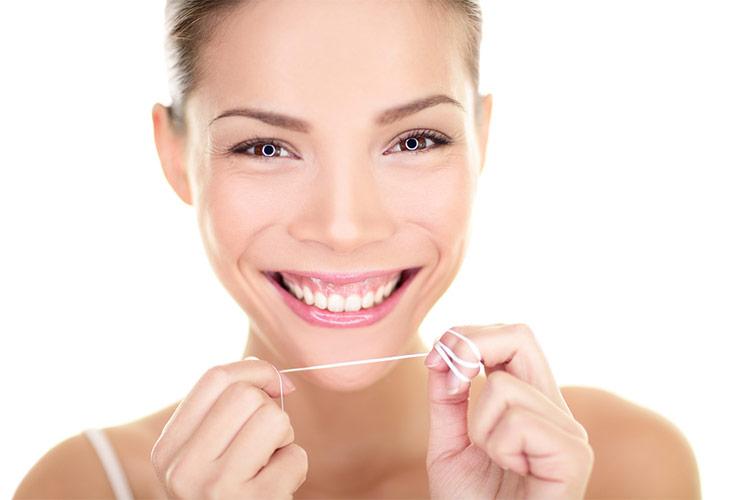 Frau mit Zahnseide beim Zahnarzt