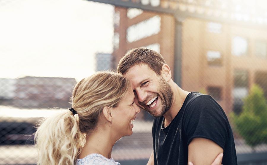 Pärchen mit schönen Zähnen freut sich über die Kosten des Implantats